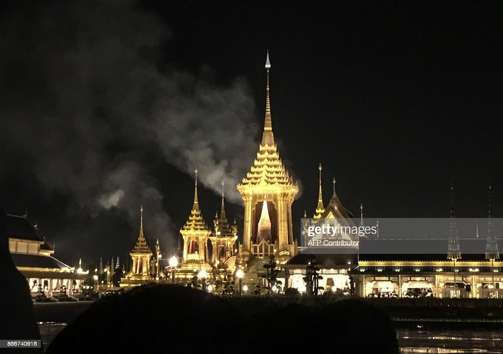 Smoke rises from the main pavilion of the cremation site where the body of late Thai King Bhumibol Adelyadej was being cremated late on October 26, 2017 in Bangkok. A sea of black-clad mourners massed across Bangkok's historic heart early on October 26 as funeral rituals began for King Bhumibol Adulyadej, a revered monarch whose passing after a seven-decade reign has left Thailand bereft of its only unifying figure. /