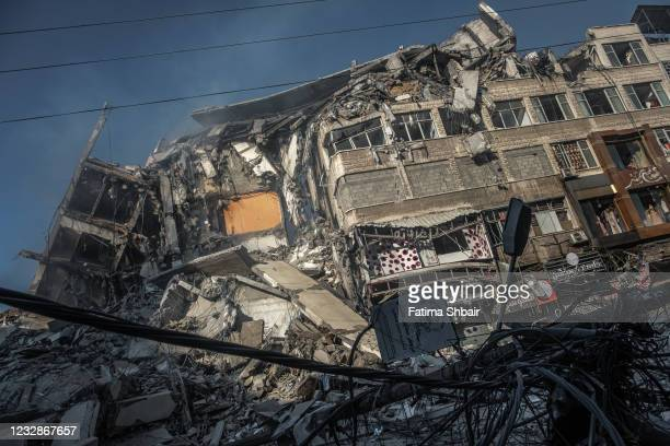 Smoke rises from the rubble of Al-Shorouk Tower following an Israeli airstrike in Gaza City, Gaza Strip on May 13, 2021 in Gaza City, Gaza. More than...