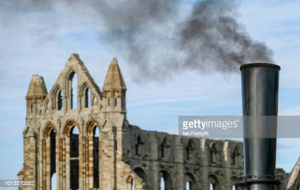 Smoke rises from the stack of a steam engine displayed in front of Whitby Abbey during the final day of the Whitby Traction Engine Rally on August 5,...