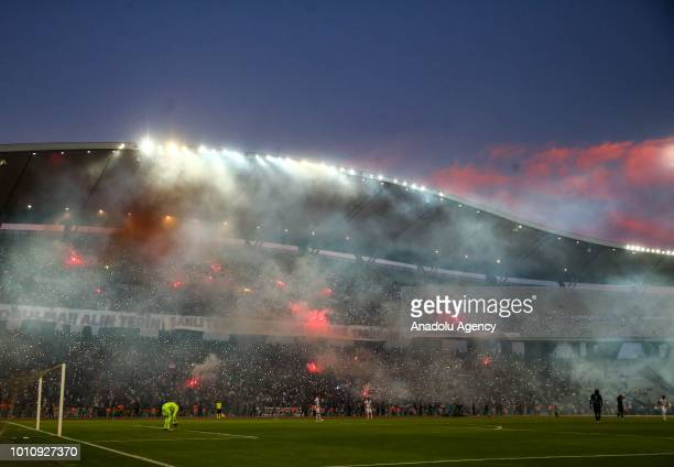 Smoke rises from the stands as Trabzonspor fans light torches during a friendly match between Trabzonspor and Cagliari at Atatürk Olympic Stadium in...