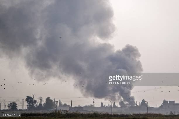 Smoke rises from the Syrian town of Tal Abyad after Turkish bombings, in a picture taken from the Turkish side of the border near Akcakale in the...