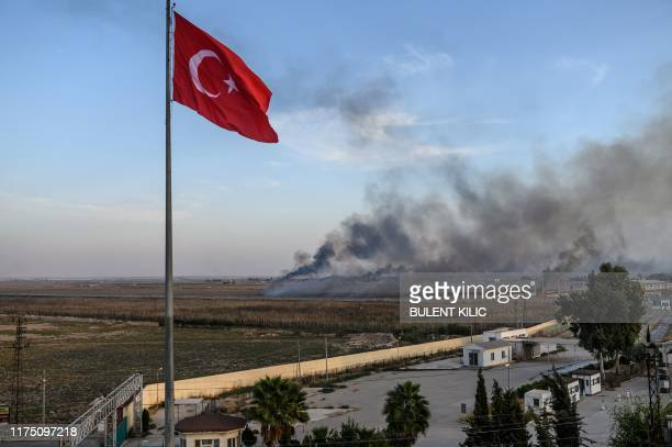 Smoke rises from the Syrian town of Tal Abyad, in a picture taken from the Turkish side of the border where the Turkish flag is seen in Akcakale on...