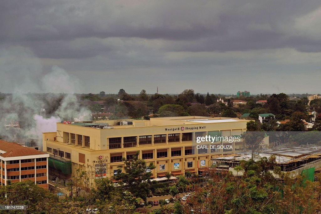Smoke rises from the Westgate mall on September 24, 2013 in Nairobi. Al-Qaeda-linked Islamist militants, claiming they were still holding hostages, on September 24 battled Kenyan troops for the fourth day of a bloody siege at the mall and threatened further attacks against the country. Sporadic gunfire and a series of explosions at the upmarket Westgate shopping center rang out throughout the day, despite officials earlier claiming Kenyan troops had wrested back 'control' of the sprawling complex from Somalia's Shebab insurgents, who are said to include Americans and a British woman. At least 65 shoppers, staff and soldiers have been killed and close to 200 wounded in the siege. AFP PHOTO/Carl de Souza / AFP / CARL