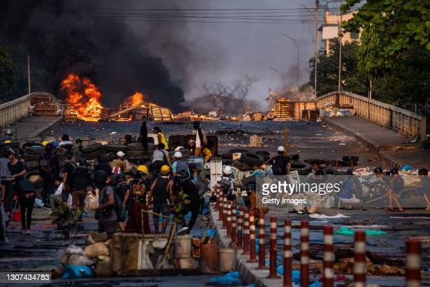 Smoke rises from tires burning at a barricade erected by protesters to stop government forces crossing a bridge on March 16, 2021 in Yangon, Myanmar....