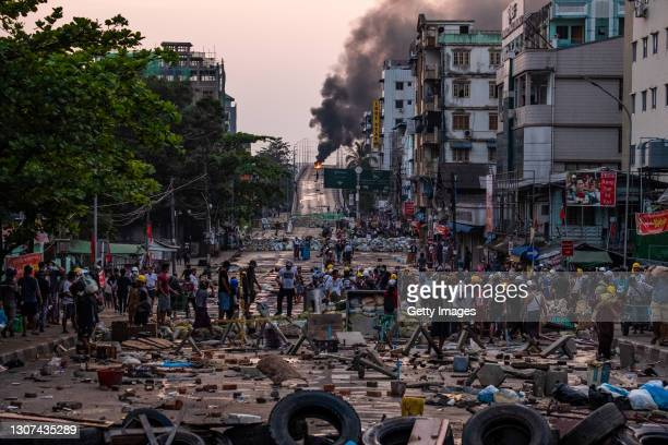 Smoke rises from tires burning at barricades erected by protesters after military junta forces attempted to breach them on March 16, 2021 in Yangon,...