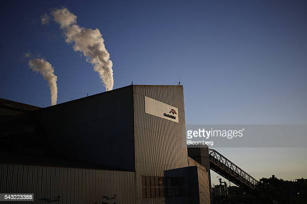 Smoke rises from towers as ArcelorMittal signage is displayed at the company's steel mill complex in Cleveland Ohio US on Friday June 24 2016...