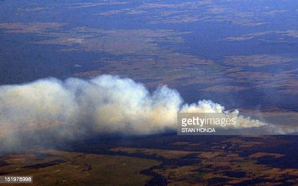 Smoke rises from what an American Airlines pilot announced are fires caused by debris from the US space shuttle Columbia as seen from an airplane...