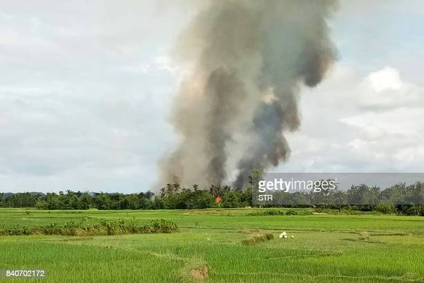 TOPSHOT Smoke rises from what is believed to be a burning village in the area near Maungdaw in Myanmar's Rakhine state on August 30 2017 At least...