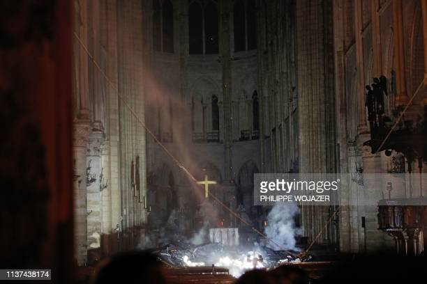 Smoke rises in front of the altar cross at NotreDame Cathedral in Paris on April 15 after a fire engulfed the building A huge fire swept through the...
