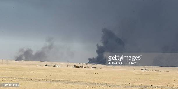 TOPSHOT Smoke rises in the background from burning oil wells as seen from the Qayyarah military base about 60 kilometres south of Mosul on October 16...