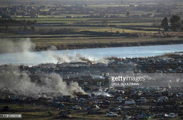 Smoke rises in the Islamic State group's last remaining position on the eastern banks of the Euphrates River in the village of Baghouz during battles...