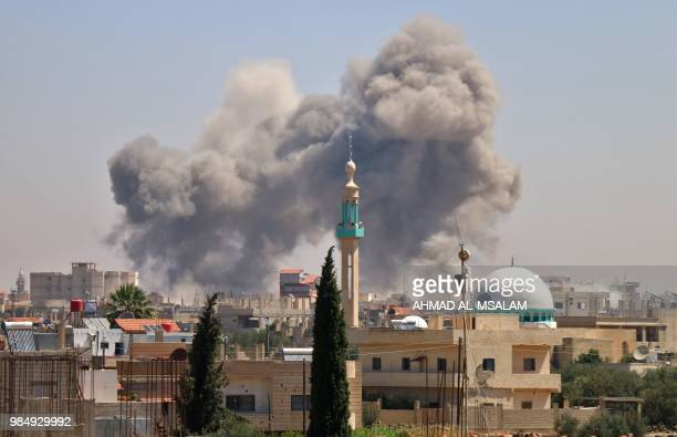 Smoke rises in the rebelheld town of Nawa about 30 kilometres north of Daraa in southern Syria on June 27 2018 during airstrikes by Syrian regime...