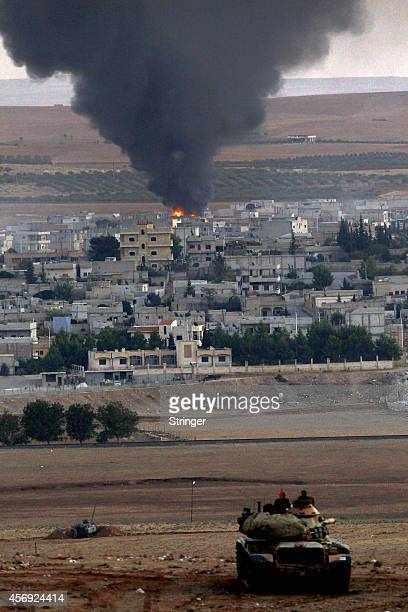 Smoke rises in the Syrian town of Kobani, seen from the Mursitpinar border crossing on October 9, 2014 on the Turkish-Syrian border in the...