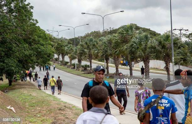 Smoke rises into the area opposite the University of Papua New Guinea as people walk away from the campus following a protest rally by the students...
