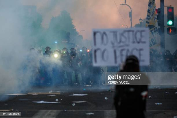 Smoke rises near a demonstrator holding a sign and facing a row of police near the 5th police precinct during a demonstration to call for justice for...
