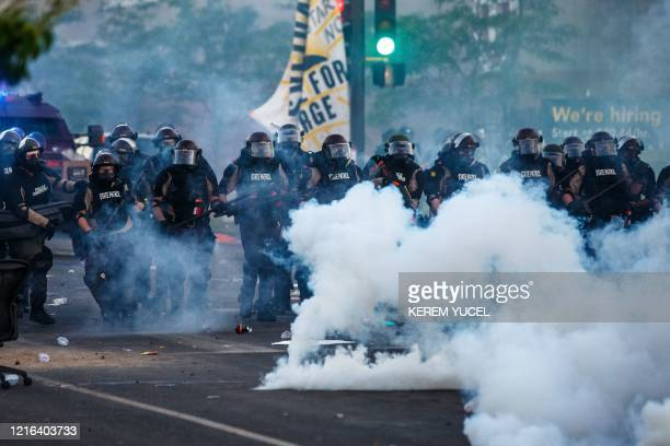 Smoke rises near a row of police in riot gear near the 5th police precinct during a demonstration to call for justice for George Floyd a black man...
