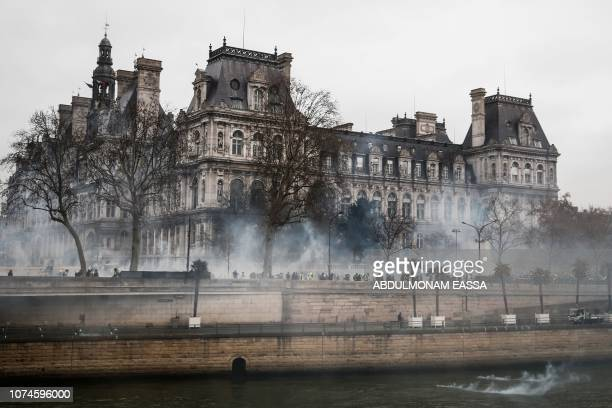 TOPSHOT Smoke rises near the City Hall in Paris during a 'Yellow Vest' antigovernment protest on December 22 as part of a nationwide day of...