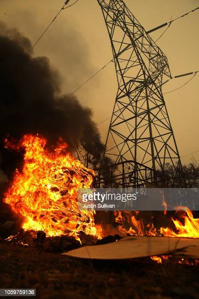 Smoke rises next to a power line tower after the Camp Fire moved through the area on November 9 2018 in Big Bend California Fueled by high winds and...