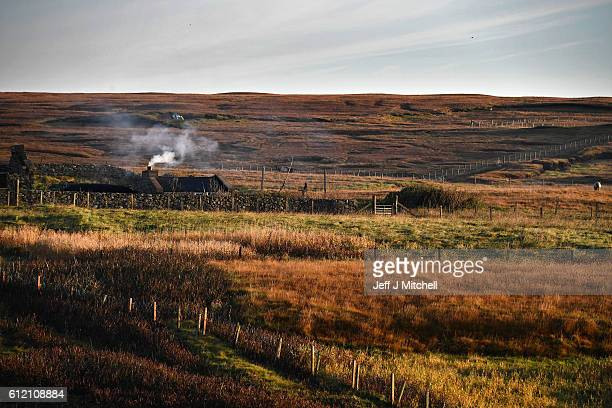 Smoke rises out a chimney of a house on the Island of Foula on October 2 2016 in Foula Scotland Foula is the remotest inhabited island in Great...