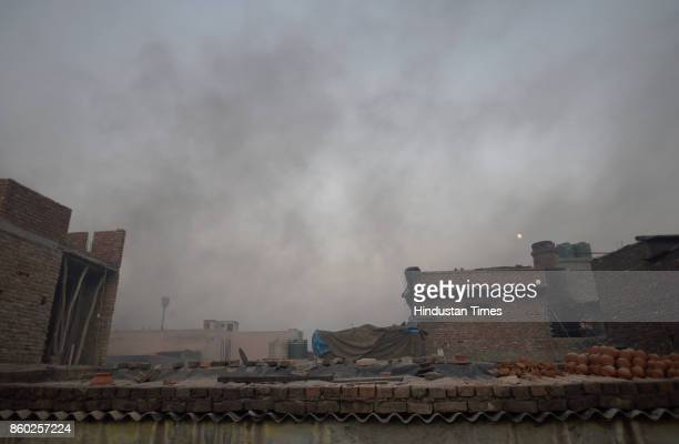 Smoke rises out of kilns of potters in West Delhi's Uttam Nagar as they are busy in making earthen diyas and other decorative items for the upcoming...