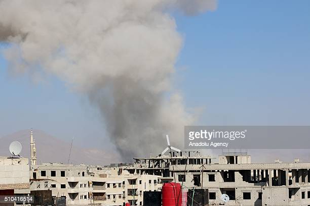 Smoke rises over a building after Assad regime war crafts carried out an airstrike over Eastern Ghouta region in Damascus Syria on February 15 2016