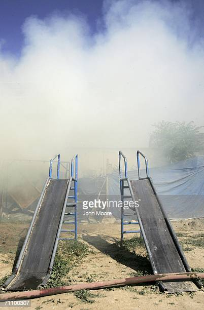Smoke rises over slides as firefighters battle a fire at the Aschiana center for working children and their families June 1 2006 in Kabul Afghanistan...