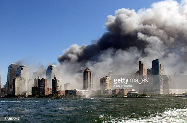 Smoke rises over the New York Skyline from the scene of the World Trade Center Attack, as seen from a tugboat evacuating people from Manhattan to New...
