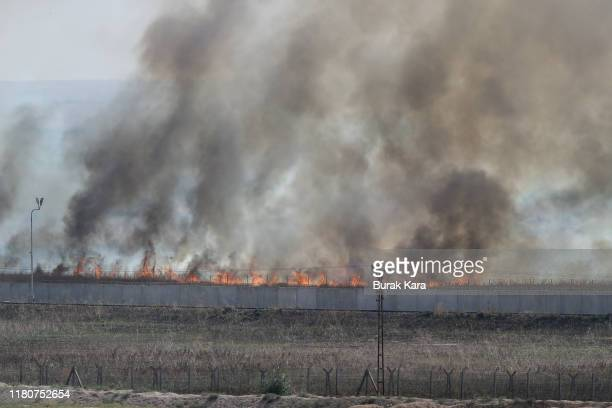Smoke rises over the outskirts of the Syrian town of Tel Abyad as seen from the Turkish border town of Akcakale on October 13 2019 in Akcakale Turkey...