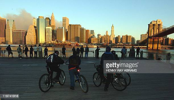 Smoke rises over the southern Manhattan skyline without the World Trade Center as members of the public watch from Brooklyn NY 12 September 2001 in...
