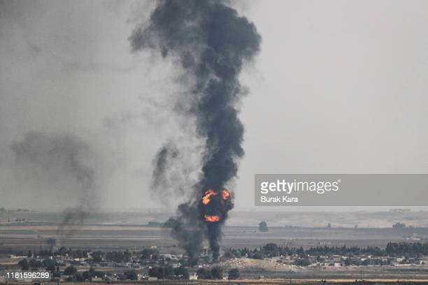 Smoke rises over the Syrian town of Ras alAin as seen from the Turkish border town on October 17 2019 in Ceylanpinar Turkey The military action is...