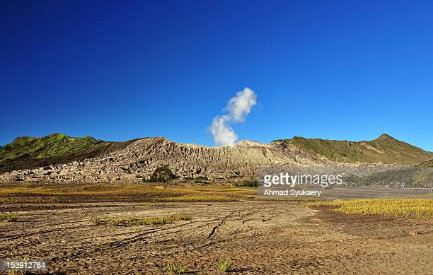 smoke rising from bromo crater - bromo crater stock pictures, royalty-free photos & images