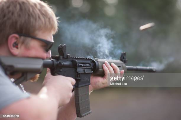 CONTENT] Smoke rising from the barrel of an AR15 assault rifle A brass casing is seen flying out