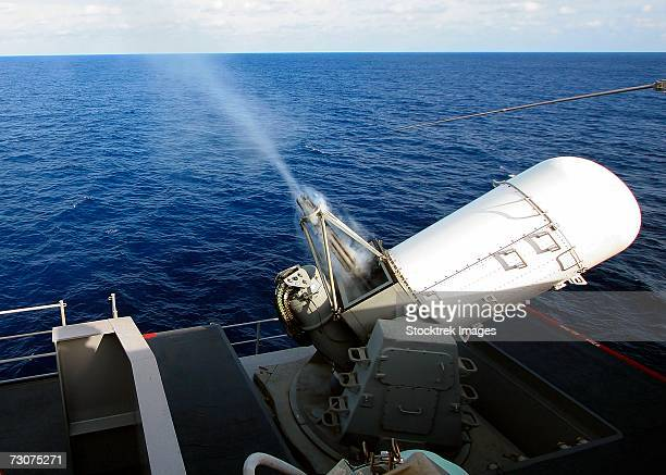 smoke rolls down the barrels of the forward-starboard-mounted mk 15 phalanx close-in weapons system (ciws) as it tracks and fires at an aerial target drone towed over the bow of the usn nimitz class aircraft carrier uss harry s. truman. - bang boat stock pictures, royalty-free photos & images