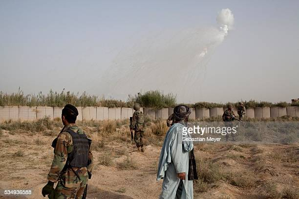A smoke screen explodes overhead of American and Afghan forces during a joint patrol in southern Pashmul Bravo 'Bonecrusher' Troop of the 175 Cavalry...