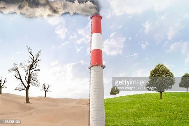 Smoke stack between desert and rural field