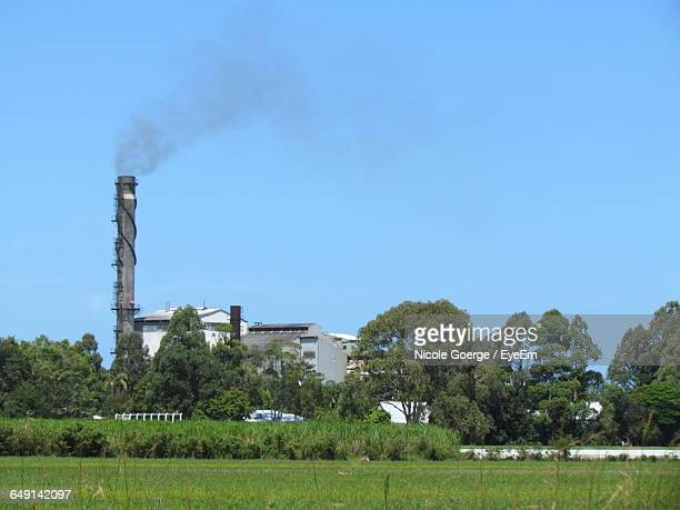Smoke Stack By Grassy Field Against Clear Blue Sky