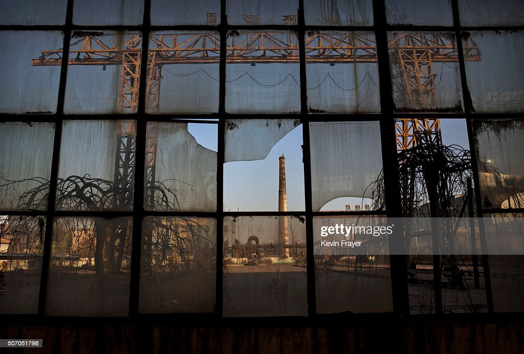 A smoke stack is seen through a broken window of a building in the abandoned Qingquan Steel plant which closed in 2014 and became one of several so-called 'zombie factories', on January 26, 2016 in Tangshan, China. China's government plans to slash steel production by up to 150 million tons, which could see the loss of as many as 400,000 jobs according to state estimates. Officials point to excessive industrial capacity, a slump in demand and plunging prices as they attempt to restructure China's slowing economy. Hebei province, long regarded as China's steel belt, once accounted for nearly a quarter of the country's steel output. In recent years, state-owned steel mills have been shut down and dozens of small privately-owned plants in the area have gone bankrupt.