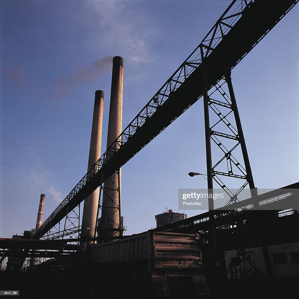 smoke stacks and other pipes stand under a clear blue sky as smoke leaves the stacks : Foto de stock