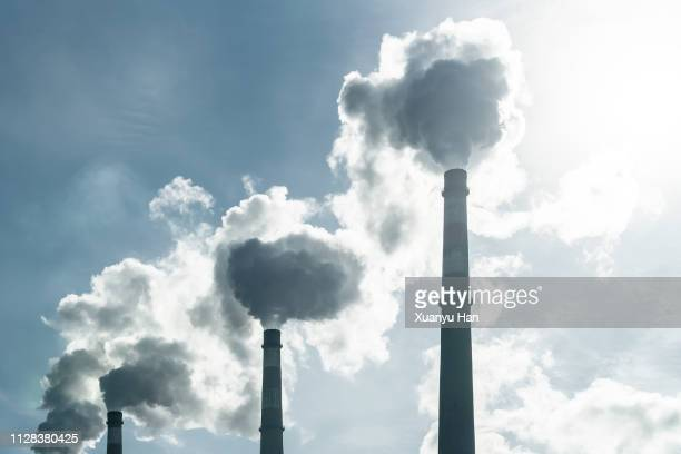 smoke stacks at a power plant. - carbon dioxide stock photos and pictures