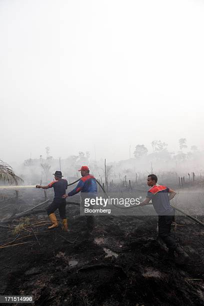 Smoke surrounds firefighters as they hose down burntoff vegetation from forest fires in Siak Riau Province Indonesia on Tuesday June 25 2013...