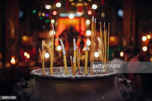 smoke swirling out of joss stick in an incense pot - man motempel stockfoto's en -beelden
