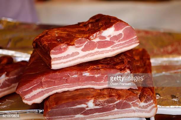 smoked bacon for sale in an outdoor produce market, paris - spek stockfoto's en -beelden