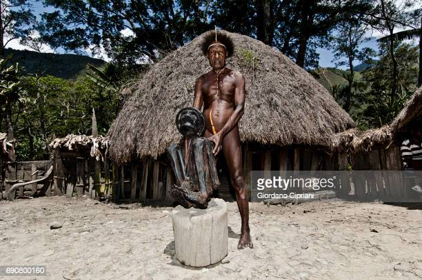smoked kurulu mummy, formerly chief of the village; the current chief of the dani tribe stands behind it. the mummy is more than 350 years old. - astuccio penico foto e immagini stock