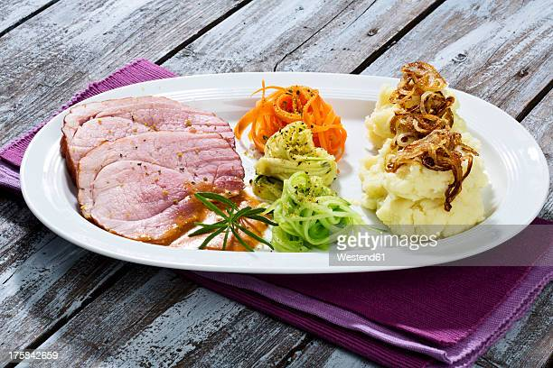 Smoked pork chop, mashed potatoes with roasted onions on plate, close up