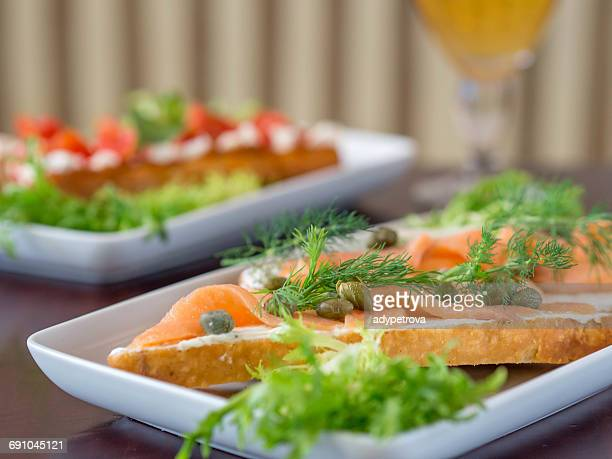 Smoked salmon and caper open sandwiches with glass of beer
