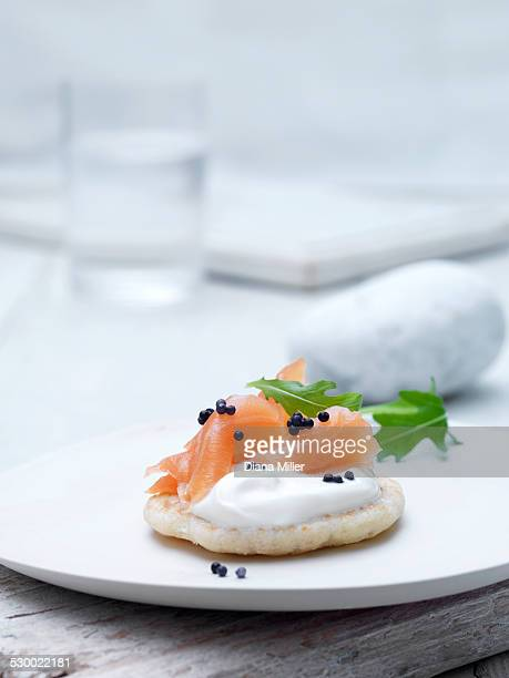 Smoked salmon and cream cheese blinis on wafer biscuit with caviar and rocket leaves garnish