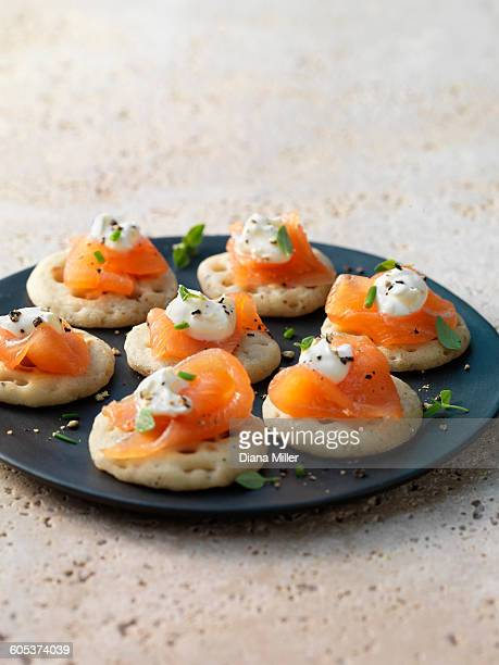 smoked salmon and cream cheese on blinis with chive and black pepper garnish - savory food stock pictures, royalty-free photos & images