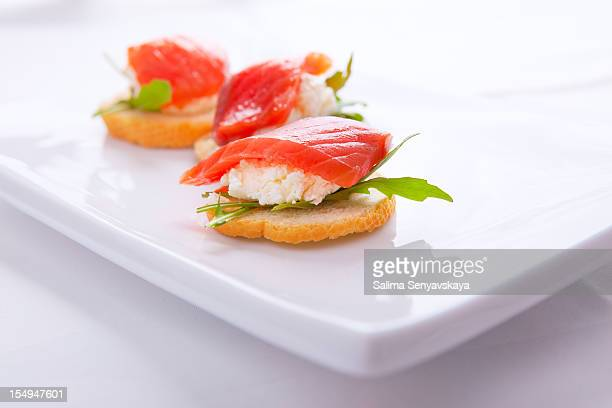 Smoked salmon appetizer on white plate on white tablecloth
