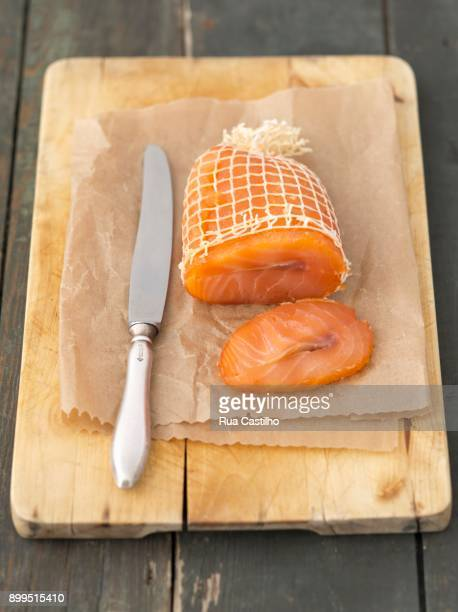 smoked salmon in a net on a chopping board - rua stock pictures, royalty-free photos & images