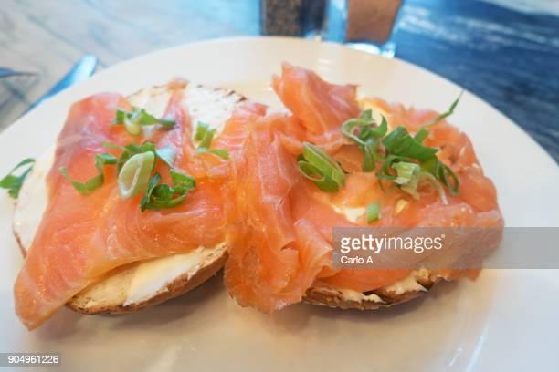 smoked salmon on bagels - salmone affumicato foto e immagini stock